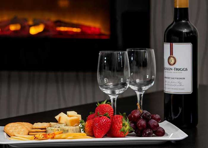 Wine bottle with platter of fresh fruit and cheese next to in-room fireplace.