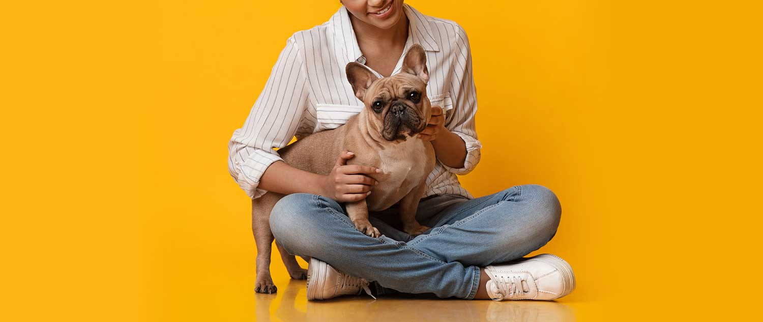 woman in tennis shoes and jeans sitting cross legged with a cute dog in her lap
